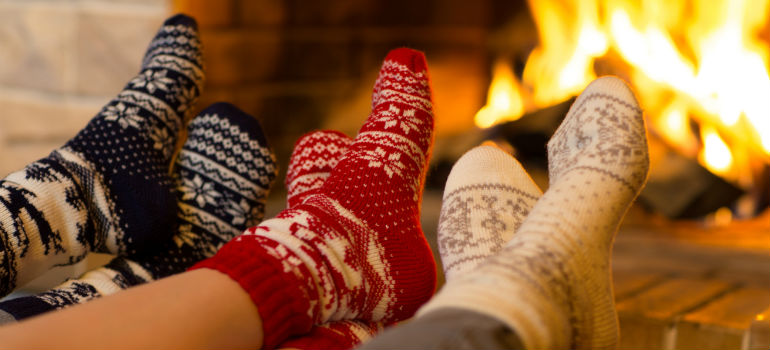 Three pairs of feet in front of the fireplace