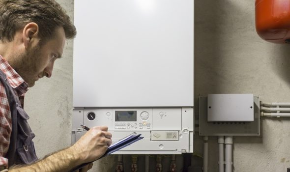 Gas-certified heating engineer who inspects a condensing boiler pipe leak